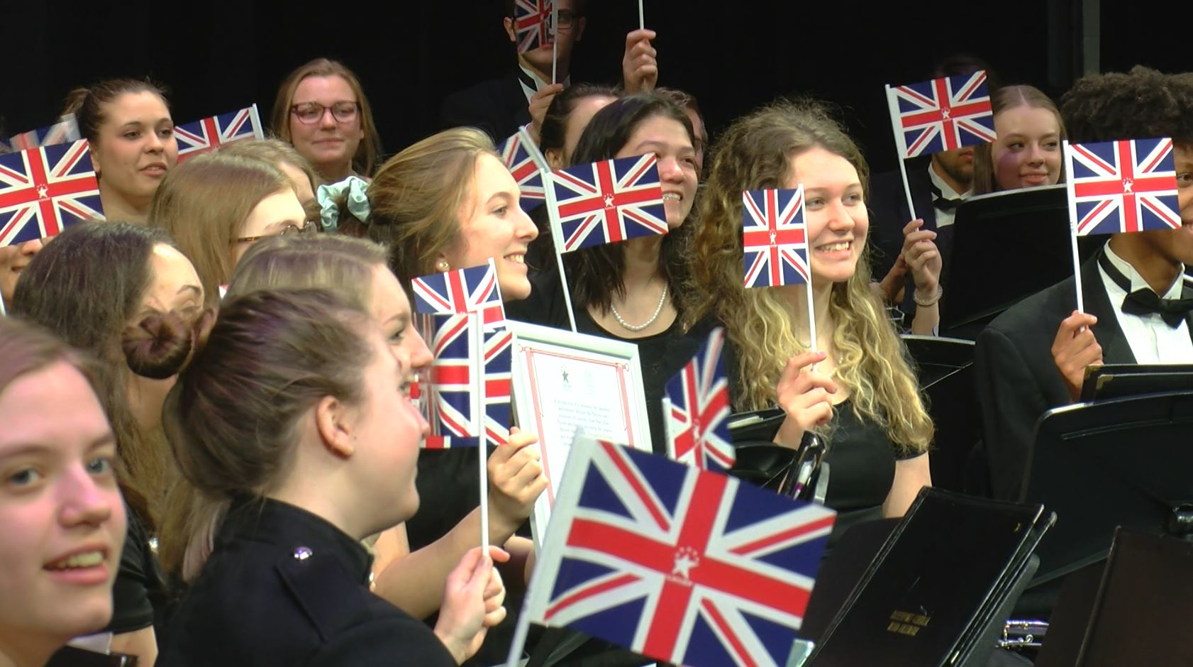 Davenport Central Marching Band hold U.K. flags during the announcement.