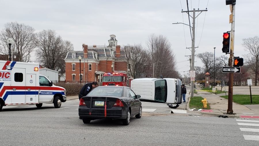 Emergency crews tend to a white van on its side as the result of an accident at Harrison and 12th Street in Davenport on April 3, 2020 (photo: Bryan Bobb, OurQuadCities.com)
