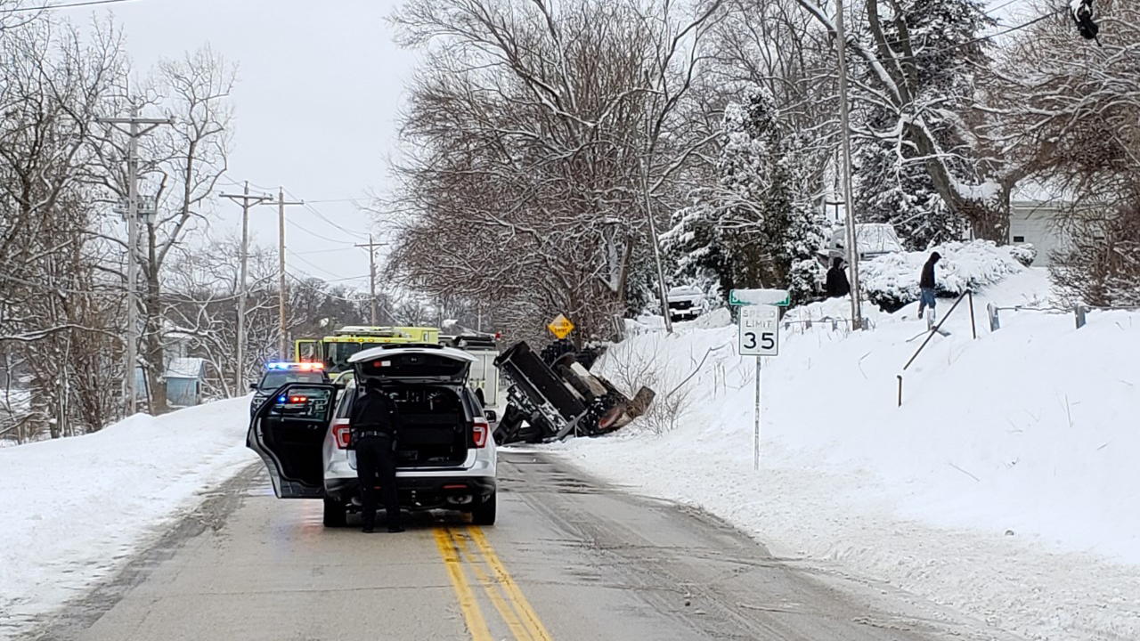 One person was taken to the hospital after a front end loader they were using to clear snow rolled down a hill onto Valley Drive in Bettendorf on January 26, 2021 (photo: Bryan Bobb, OurQuadCities.com).