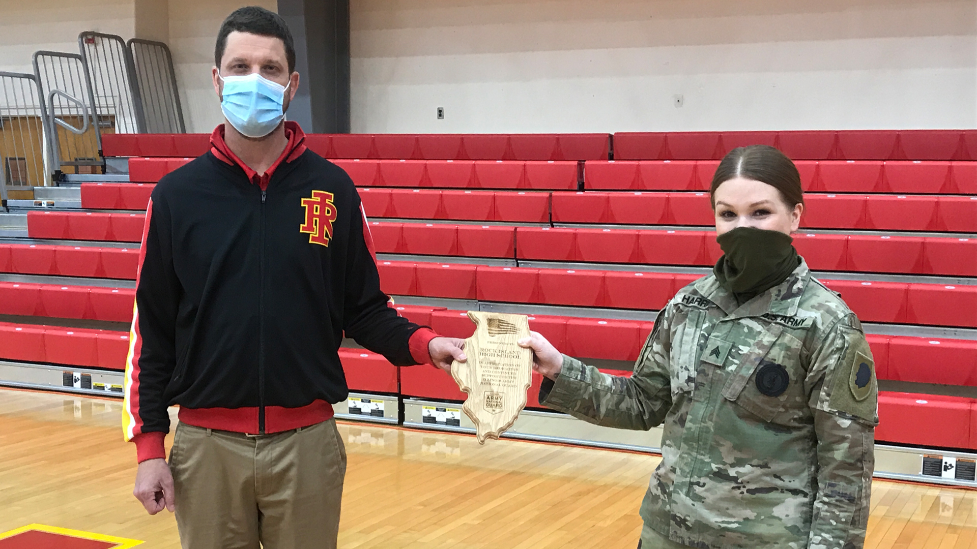 Rock Island High School Principal Jeff Whitaker accepts an award from Sergeant Jessica Harris with the Illinois Army National Guard on January 22, 2021.